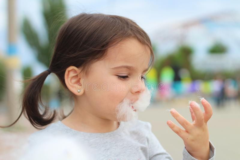 Little funny white girl with tails with narrow eyes holds cotton candy with his lips while walking outdoors royalty free stock photo