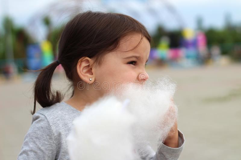 Little funny white girl with tails with narrow eyes holds cotton candy with his lips while walking outdoors stock photos