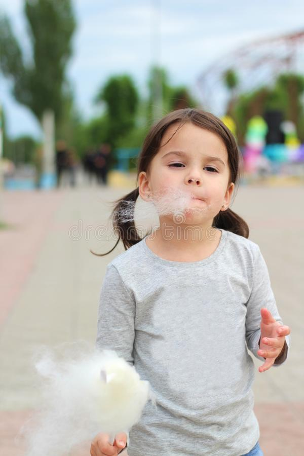 Little funny white girl with tails with narrow eyes holds cotton candy with his lips while walking outdoors royalty free stock photos