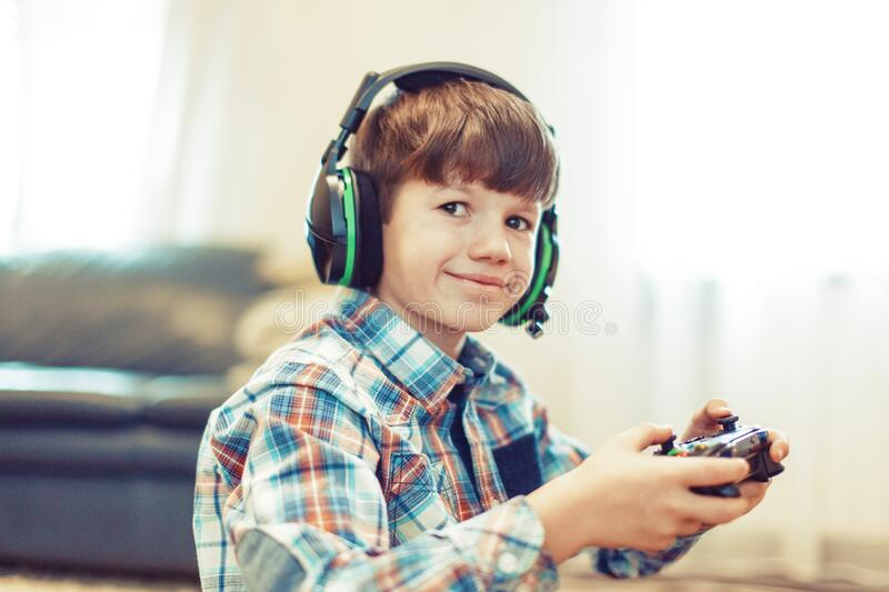 Little gamer boy in headset holding controller royalty free stock photos