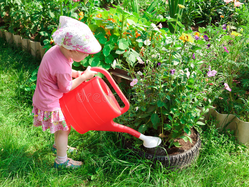 Little gardener. With a big red bailer stock photography