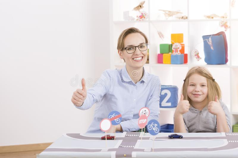 Little genius learning traffic regulation. Smart little genius learning traffic regulations with young female teacher royalty free stock image