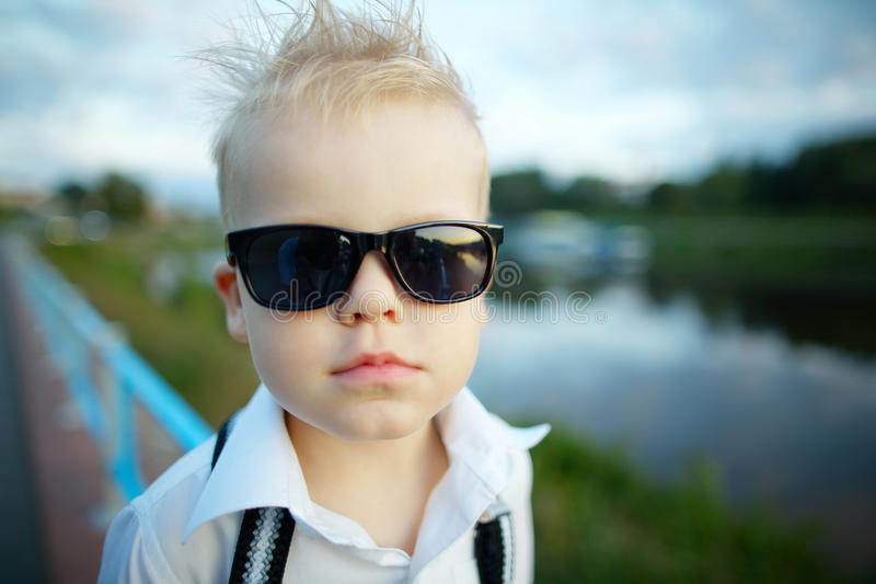 Little gentleman with sunglasses outdoors. Photo of little gentleman with sunglasses outdoors portrait royalty free stock photo