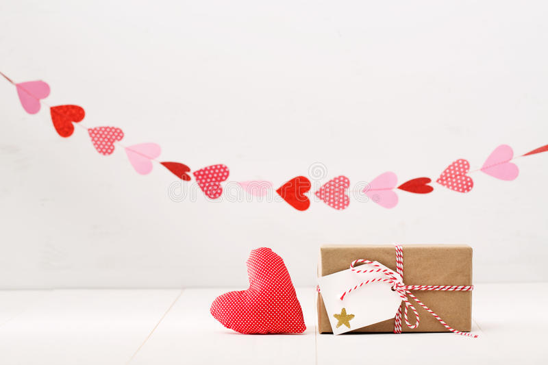Little gift box with hearts hanging above stock photo