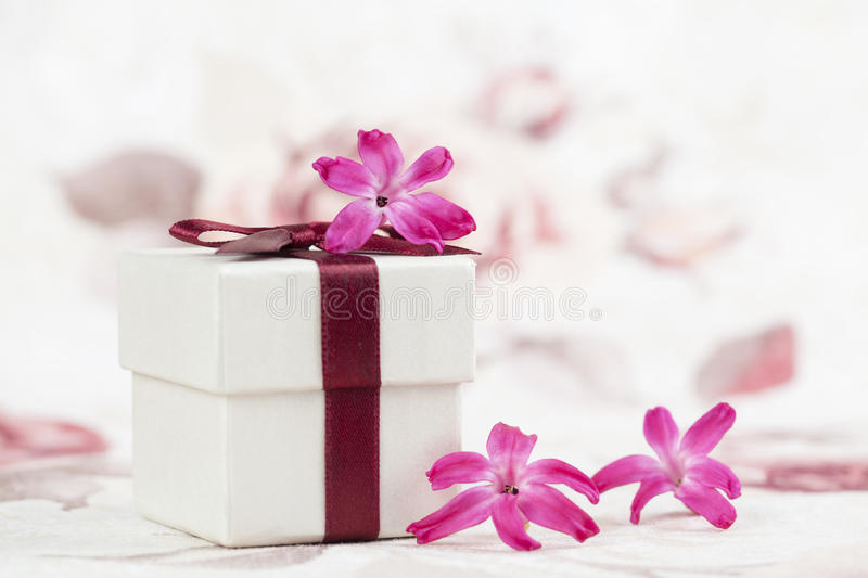 Little gift. Gift box and little pink hyacinth flowers. Shallow dof stock photos
