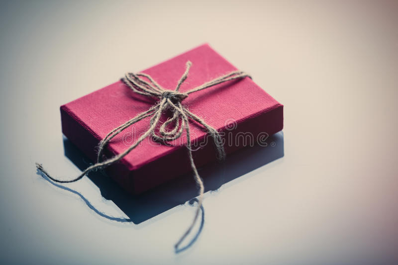 Little gift box on white glass royalty free stock photography