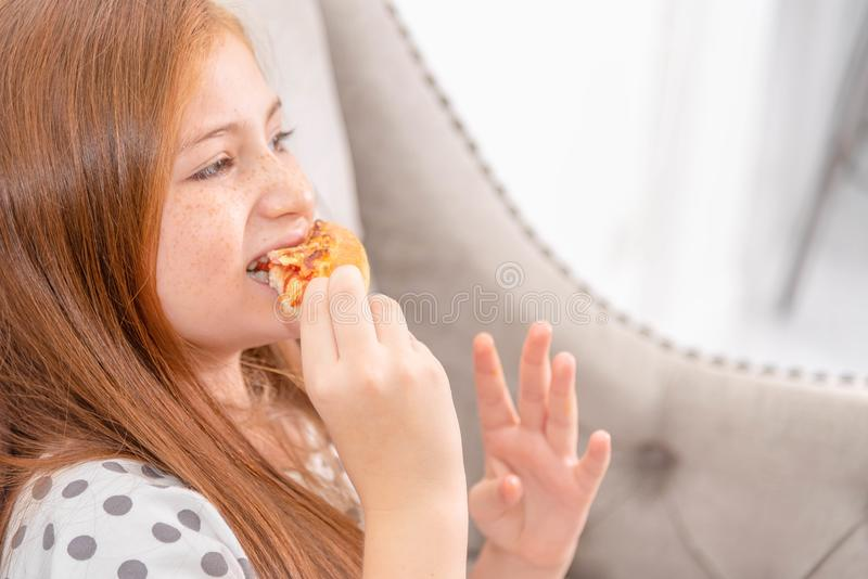 Little gilr happy and enjoying eating pizza. Delivery food, junk royalty free stock photo