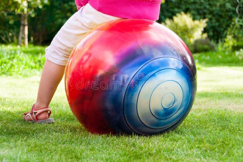Little gilrl jumping on ball stock image