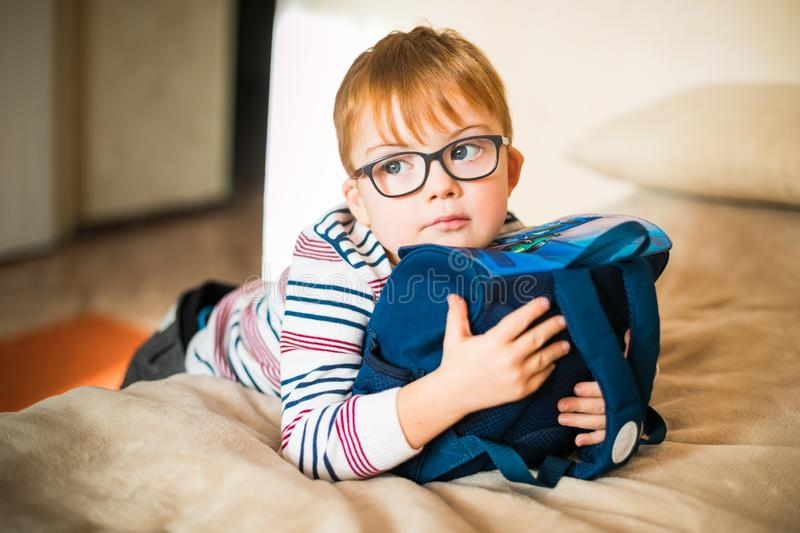 Little ginger boy in the glasses with syndrome dawn playing with backpack royalty free stock photography