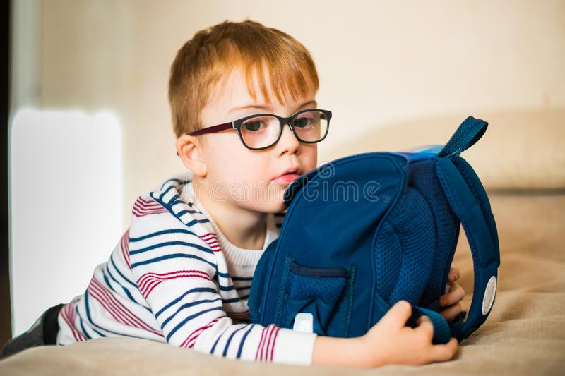 little ginger boy in the glasses with syndrome dawn playing with backpack royalty free stock photo