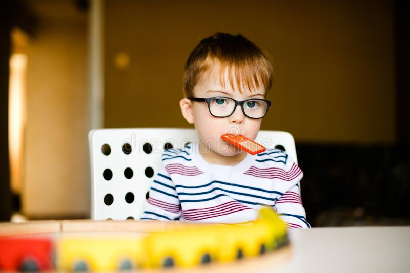 Little ginger child boy in the glasses with syndrome dawn playing with wooden railways royalty free stock image