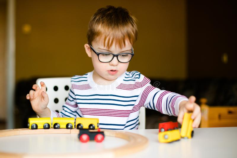 little ginger child boy in the glasses with syndrome dawn playing with wooden railways royalty free stock photo