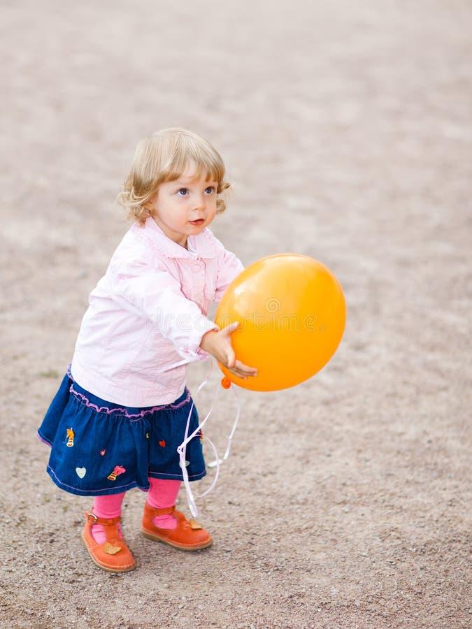 Little girl. With orange balloon - shallow DOF stock photography