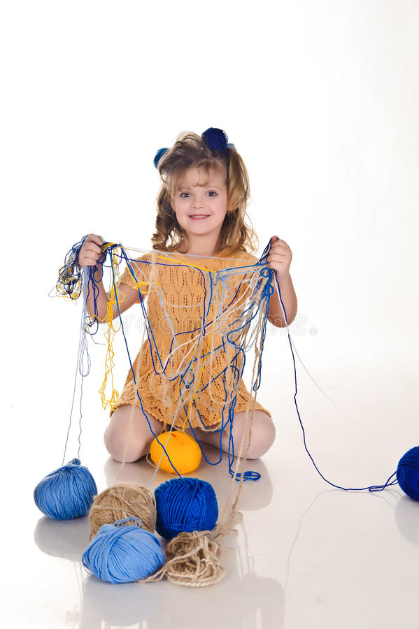 Little girl. S play with balls of wool royalty free stock photography