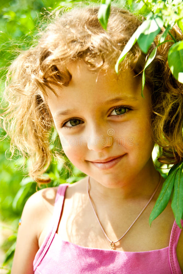 Little girl. Smiling little girl with green leaves outdoors stock photo