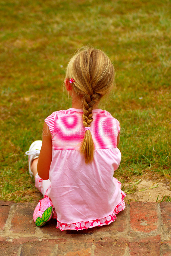 Little girl. Back view of a cute little girl with ponytail dressed in pink clothes and sitting on the stones of a staircase outdoors stock photography