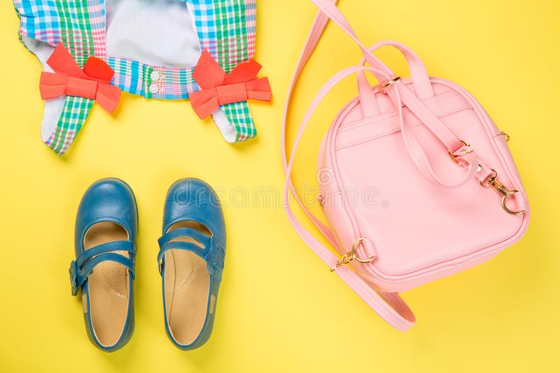 Little girl accessories. Pink bag with colorful dress and shoes on yellow background. Top view stock photos
