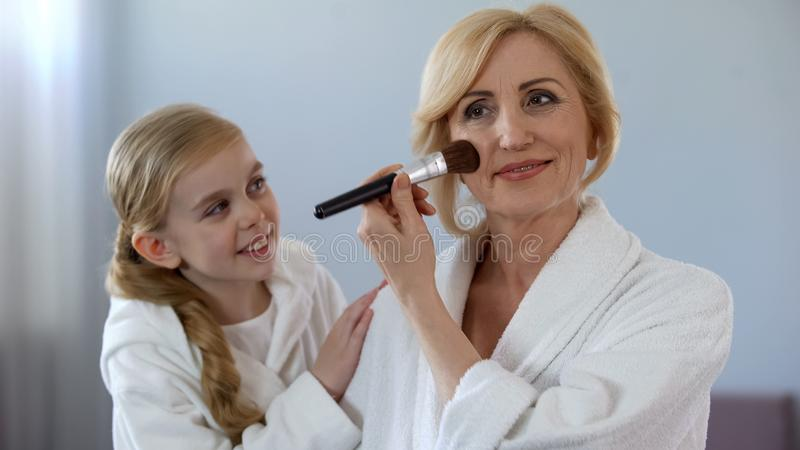 Little girl admiring her beautiful grandmother applying face powder, beauty stock images