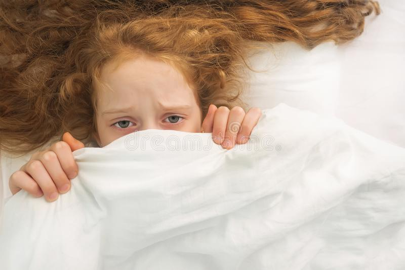 Little girl afraid sleeping and pulling quilt on head. Sad little girl afraid sleeping and pulling quilt on head royalty free stock photo