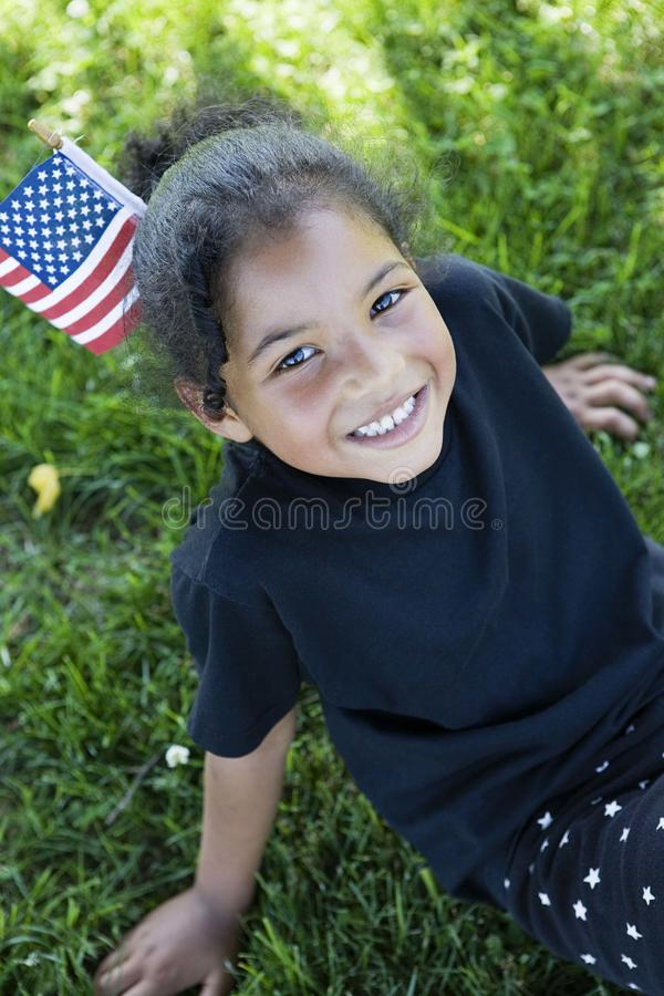 Little girl with American Flag. Little girl sitting in the grass with a small American Flag stuck in her hair royalty free stock image