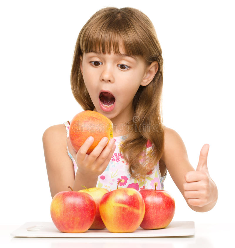 Little girl with apples is showing thumb up sign royalty free stock image