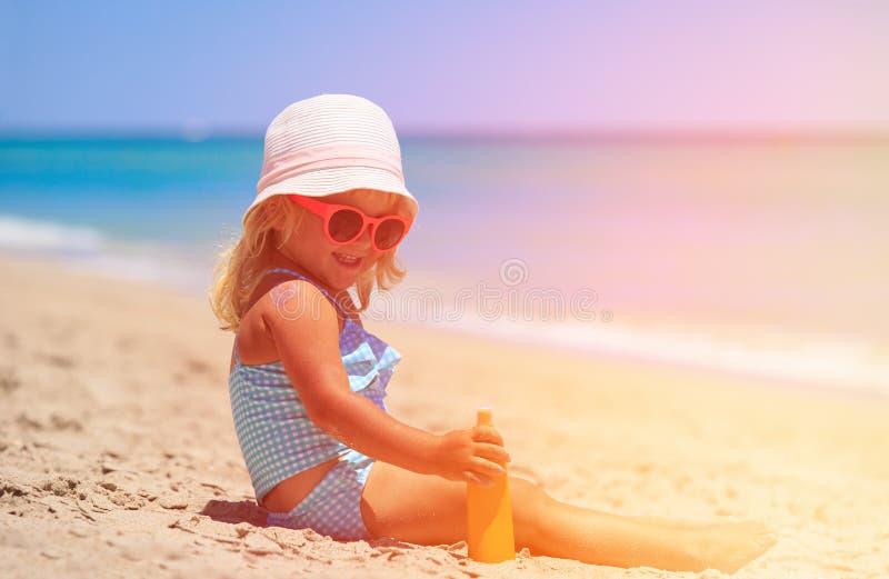 Little girl applying sunblock cream on shoulder stock image