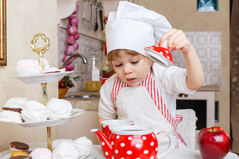 Download Little Girl In Apron In The Kitchen. Stock Photo - Image: 39869500