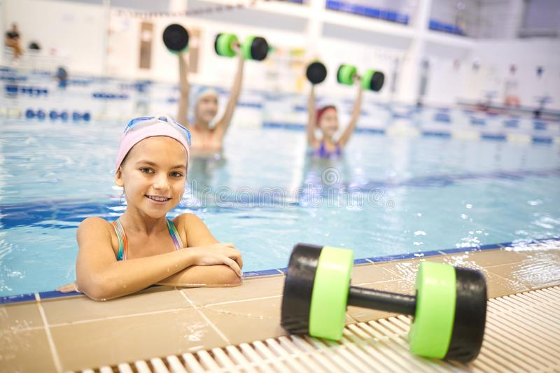 Little girl at aqua aerobics. Portrait of smiling little girl standing in the water near the edge of the pool with other girls doing aqua aerobics in the stock photography