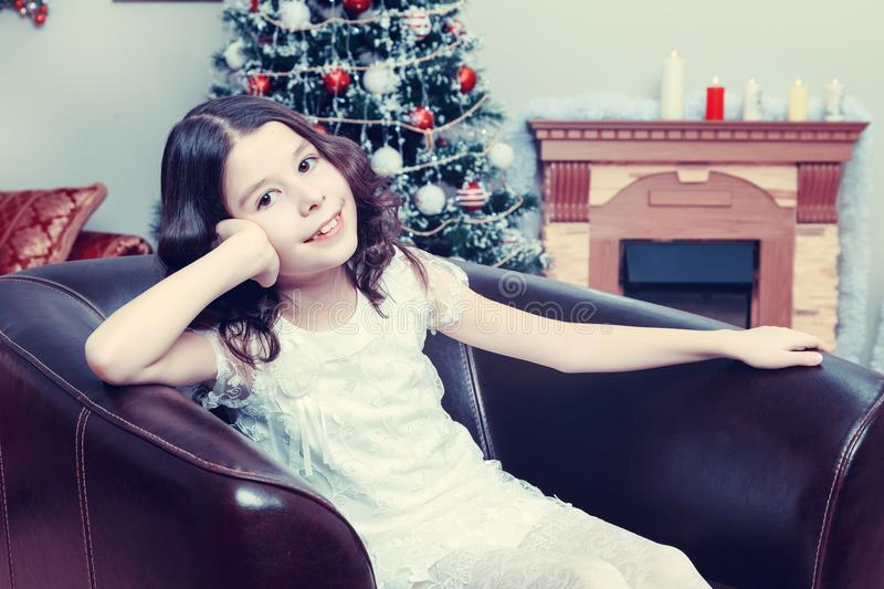 The little girl in the armchair by the Christmas tree. royalty free stock photography