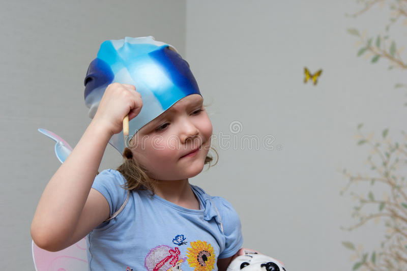 Little girl artist with brush in hand in rubber cap. Little girl artist with a brush in hand in a rubber cap stock images