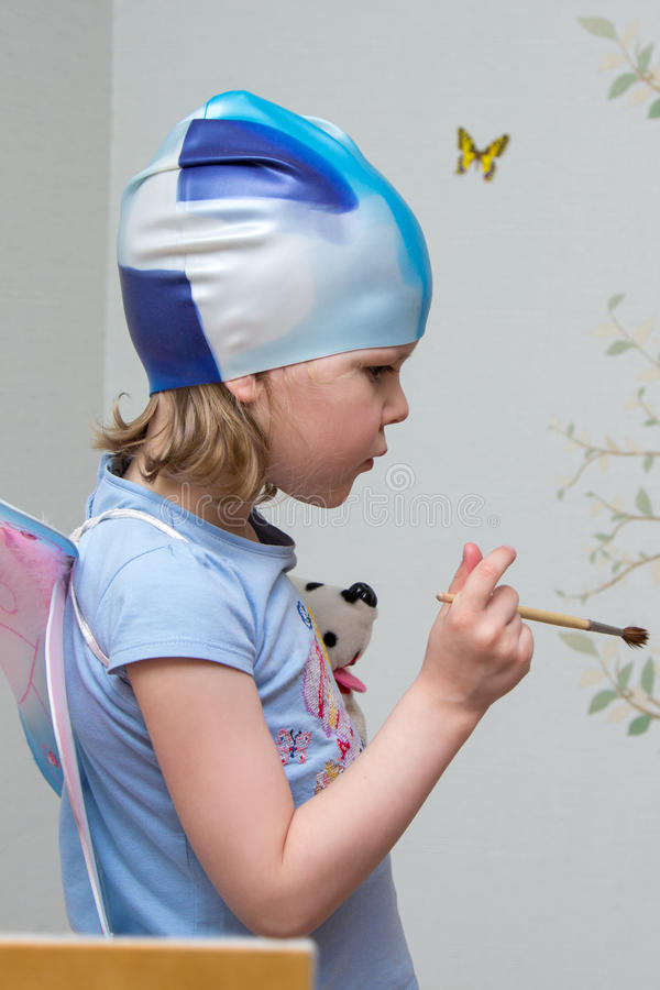 Little girl artist with brush in hand in rubber cap. Little girl artist with a brush in hand in a rubber cap royalty free stock photo