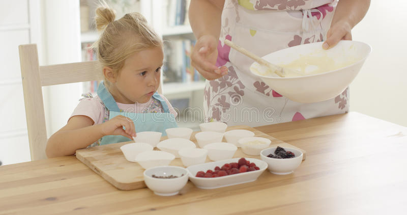 Little girl assisting Mum with the baking stock photos