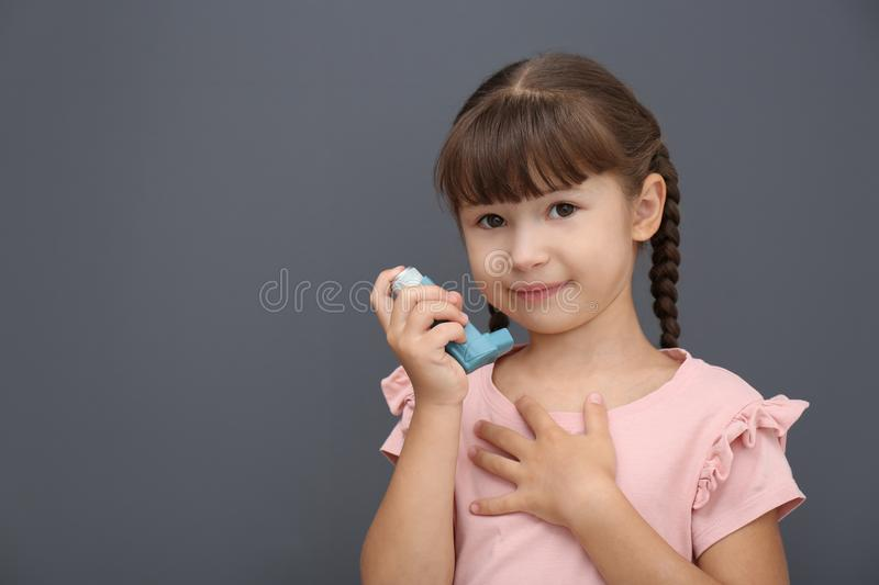Little girl with asthma inhaler stock photos