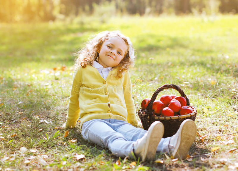 Little girl with autumn basket and apples stock photography