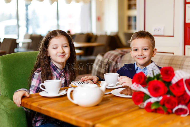 Little girl with a baby boy , sitting at the table and drank tea with Cake royalty free stock photo