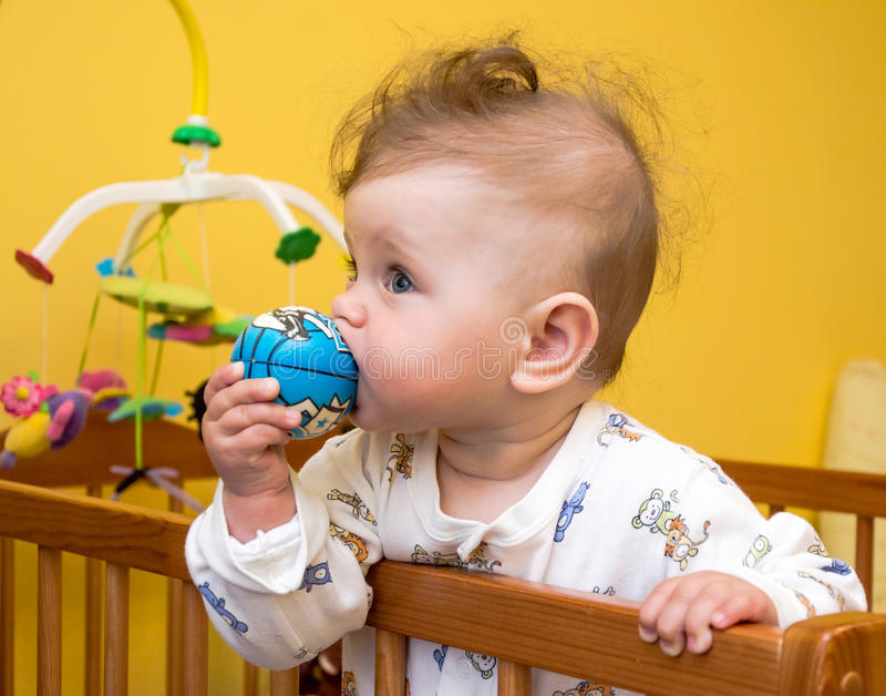 Little girl baby chews the ball in the crib. Girl baby chews the ball in the crib stock photo