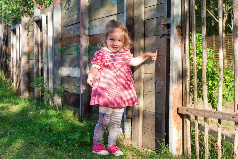Little girl baby shows a finger on the gate in the fence stock photos