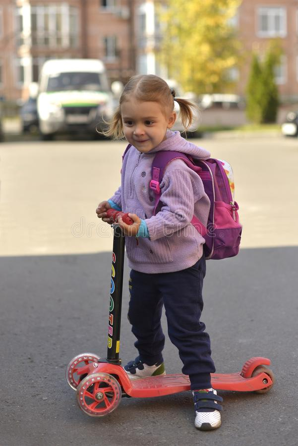 A little girl with a backpack riding a scooter. A little girl with a backpack riding a scooter and smiling royalty free stock photo