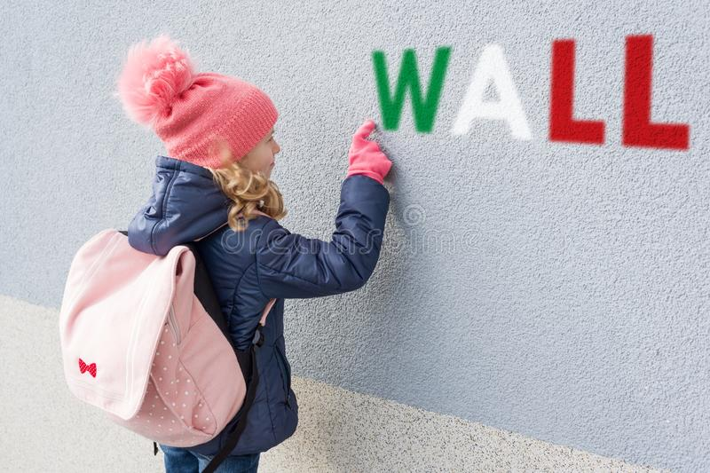 Little girl with a backpack, showing a finger on the gray wall, side view. stock image