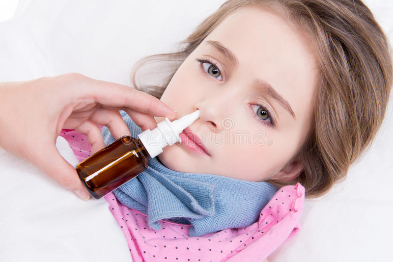 Little girl with bad cold using nasal drops. royalty free stock image