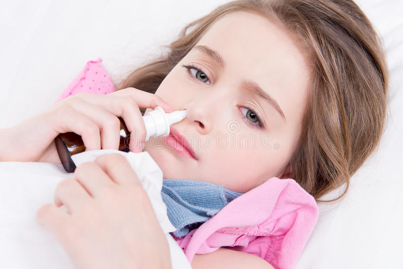 Little girl with bad cold using nasal drops. Little girl with bad cold lying in bed andusing nasal drops on white background royalty free stock image