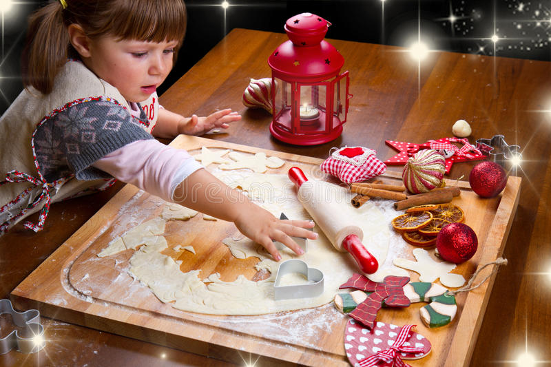 Little girl baking Christmas cookies cutting pastry stock photo