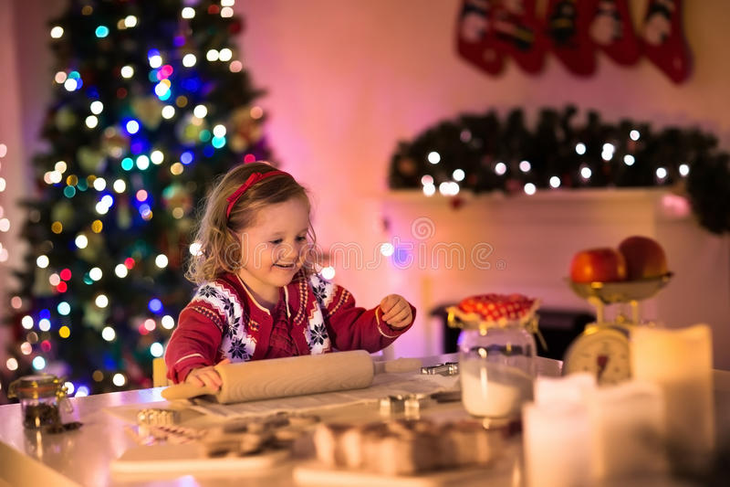 Little girl baking Christmas pastry. Children bake gingerbread. Toddler child preparing cookie for family dinner on Xmas eve. Decorated kitchen or dining room stock photo