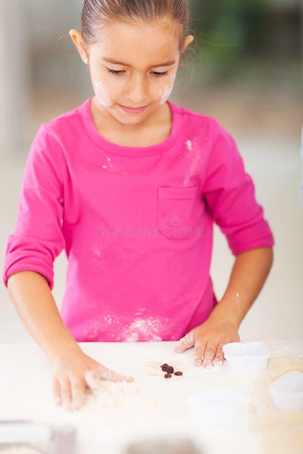 Little girl baking cookies. Cute little girl baking cookies in kitchen stock photo