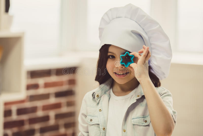 Little girl baking. Cute little girl in chef hat is holding dough cutters, looking at camera and smiling while baking in the kitchen stock image