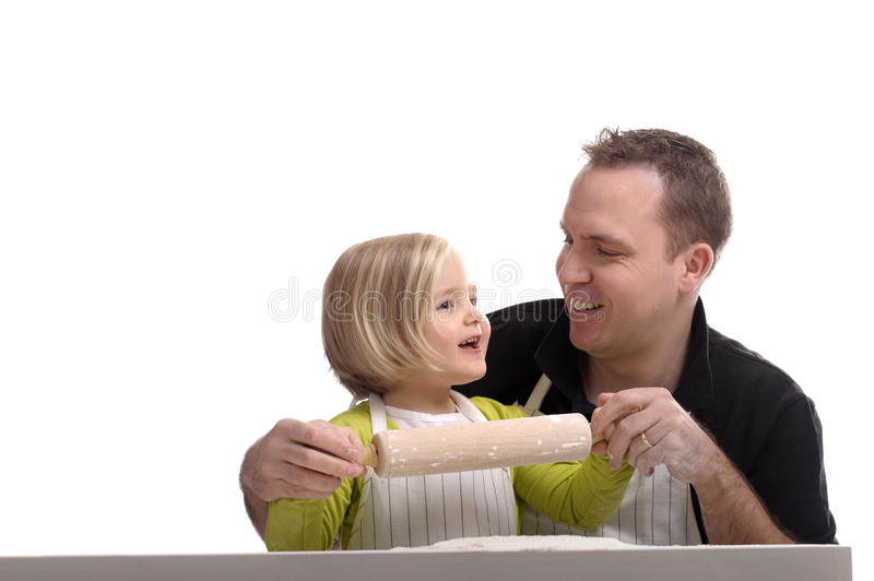 Little girl baking with her daddy. Isolated on white stock image