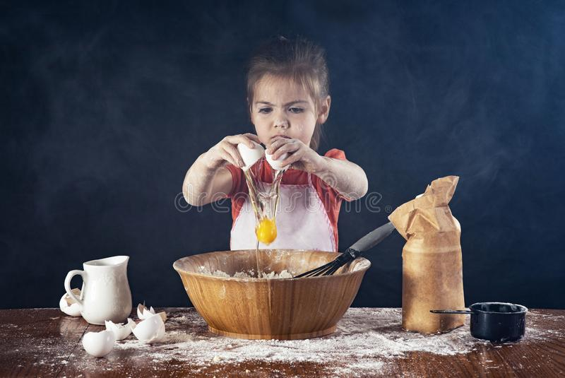 Little girl baking in the kitchen. A little girl breaks an egg into a large bowl in the kitchen and makes a mess royalty free stock photo