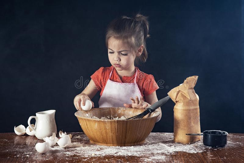 A little girl baking in the kitchen. A litlte girl cracks open an egg into a bowl in the kitchen stock images
