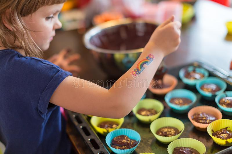 Little girl baking muffins. At home stock photo