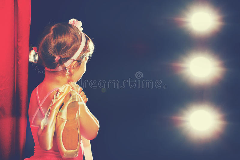 Little girl ballerina ballet dancer on stage in red side scenes. Little child girl ballerina ballet dancer on the stage in red side scenes and looking in odeum stock images